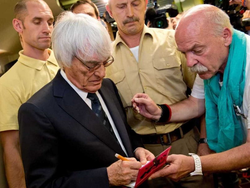 Formula One Chief Executive Bernie Ecclestone signs an autograph after leaving the courtroom at the regional court in Munich, southern Germany, on August 5, 2014.