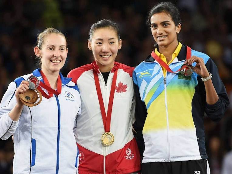 Canadas Michelle Li, gold medallist, is flanked by Scotlands Kirsty Gilmour, left, silver medalist, and Indias PV Sindhu, right, bronze medallist, after the womens singles badminton final at the Commonwealth Games in Glasgow, Scotland on Sunday, August 3, 2014.