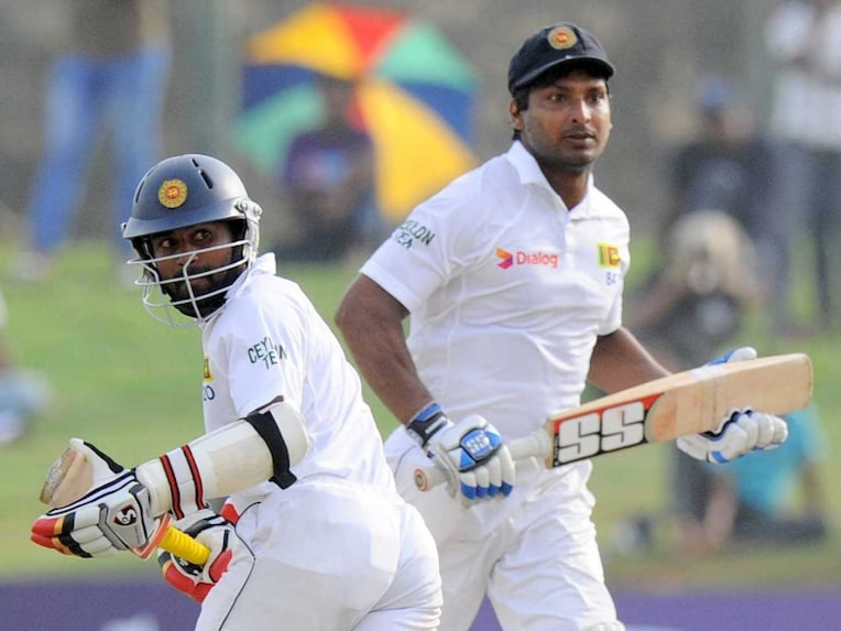 Sri Lankan cricketers Kumar Sangakkara (R) and Kaushal Silva run between wickets during the second day of the opening Test match between Sri Lanka and Pakistan at the Galle International Cricket Stadium.
