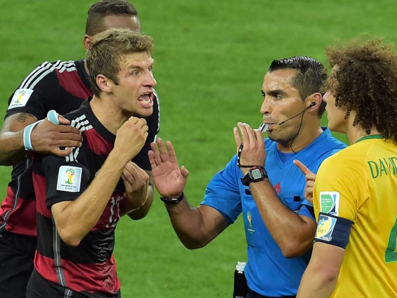 Mexican referee Marco Rodriguez stands in between Brazil's defender David Luiz (R) and Germany's forward Thomas Mueller (L) arguing during the semi-final