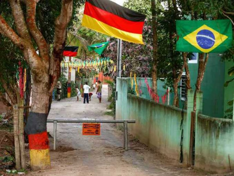 Residents and a Brazilian military policeman stand behind a barrier on a road in front of Germany's national soccer team's Campo Bahia base camp in the village of Santo Andre north of Porto Seguro
