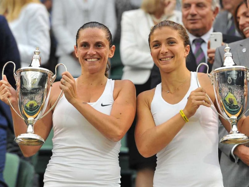 Italys Sara Errani (R) and Roberta Vinci hold their winners trophies during the presentation after winning their Wimbledon 2014 womens doubles final.