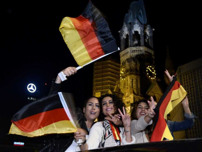 German fans celebrate with national flags on a car near the Zoo train station on early July 14, 2014 in Berlin after Germany won the FIFA World Cup 2014 final football match against Argentina in Brazil.
