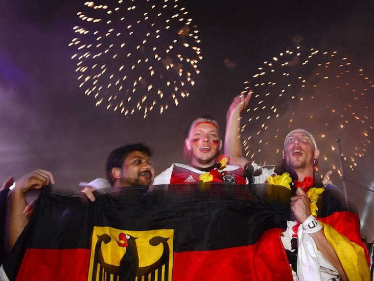 German fans celebrate during a firework after an outdoor screening near the Brandenburg Gate in Berlin, on July 13, 2014, as Germany won the FIFA World Cup 2014 final football match against Argentina played in Brazil. More than 200,000 Germany fans thronged in central Berlin for the World Cup final, turning an avenue behind the Brandenburg Gate into a sea of black, red and gold flags. Germany won 1-0.