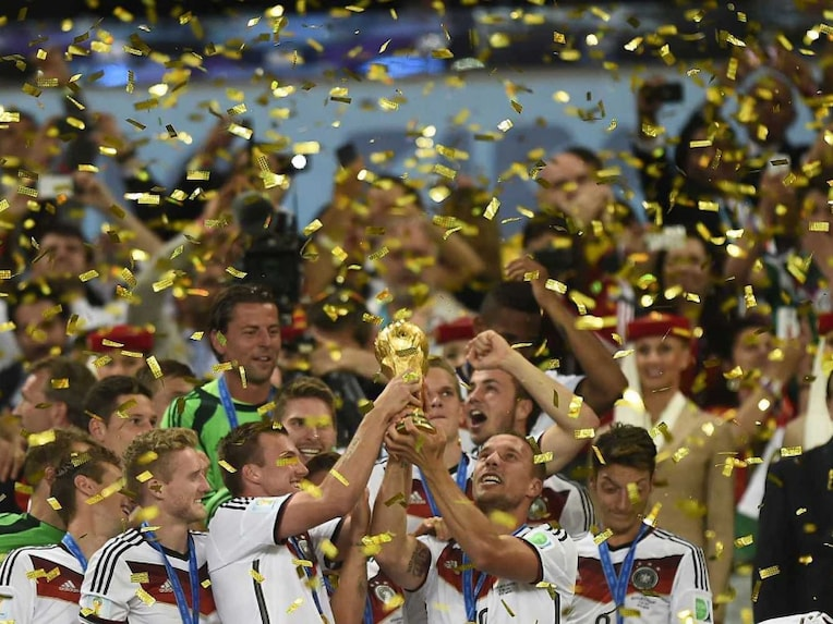 Germanys team players hold up the World Cup trophy as they celebrate after winning the 2014 FIFA World Cup final football match between Germany and Argentina 1-0 following extra-time at the Maracana Stadium in Rio de Janeiro, Brazil, on July 13, 2014.