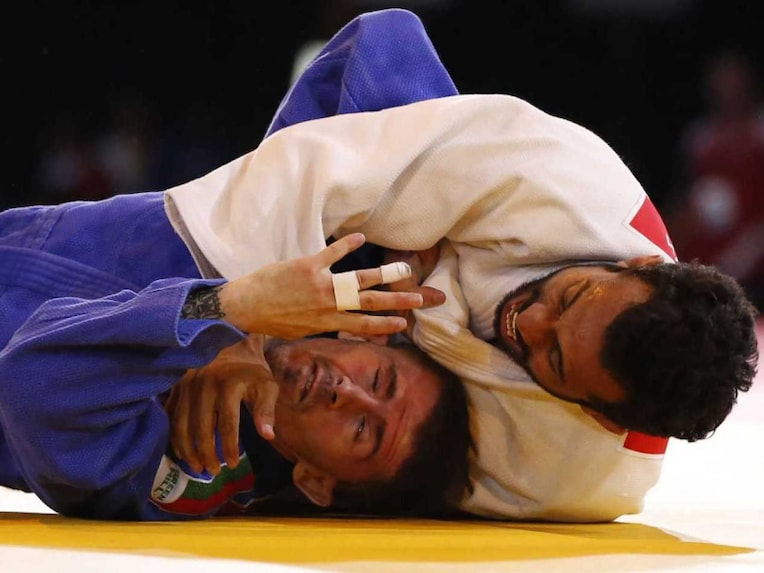 Navjot Chana of India, right, holds down Brandon Dodge of Wales during their mens 60 kg judo quarterfinal bout at the Commonwealth Games Glasgow 2014, in Glasgow, Scotland Thursday, July, 24, 2014.
