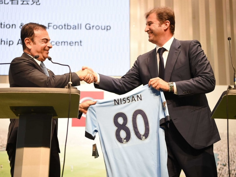 Ferran Soriano (R), CEO of City Football Group, which owns Manchester City Football Club, gives a Manchester City shirt to Carlos Ghosn (L), CEO and president of Nissan Motor, during their joint press conference at Nissan's headquarters in Yokohama, suburb of Tokyo, on July 17, 2014.