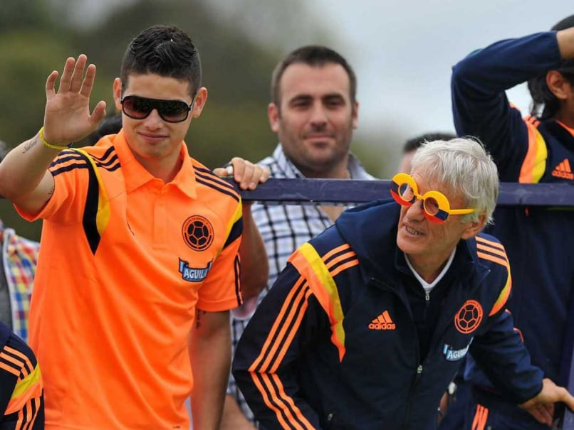 Colombian football player James Rodriguez (L) waves at fans next to team coach Nestor Pekerman (C) and teammate Able Aguilar (R) upon their arrival in Bogota after the FIFA World Cup Brazil 2014, on July 6, 2014.