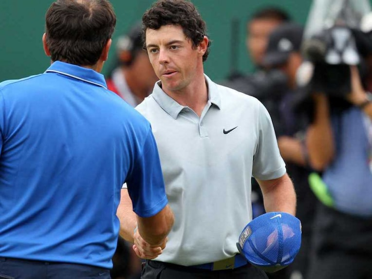 Northern Ireland's Rory McIlroy (R) shakes hands with Italy's Francesco Molinari on the 18th green after his third round 68, on day three of the 2014 British Open Golf Championship