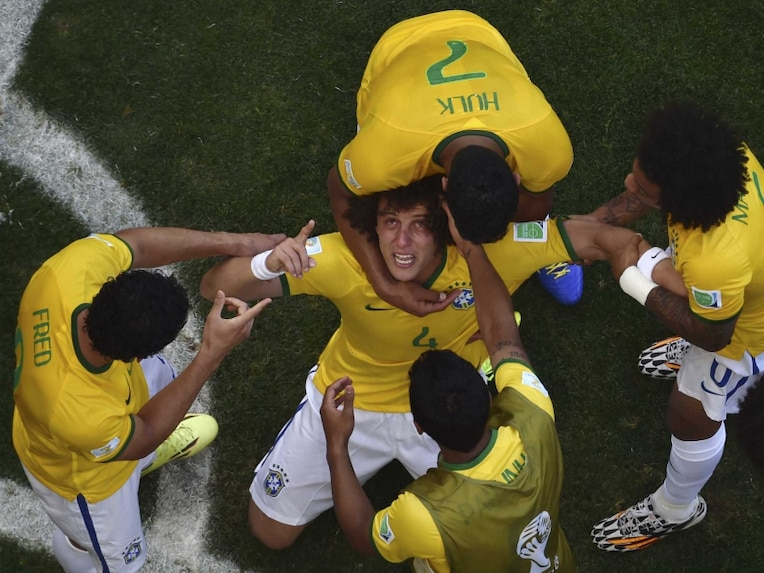 Brazils David Luiz is surrounded by teammates after Brazils first goal during the FIFA World Cup Round of 16 match vs Chile.