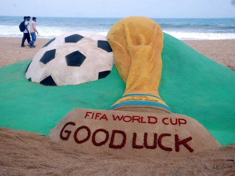 Sand artist Sudarsan Pattnaik creates a sculpture on FIFA World Cup at Puri beach in Odisha.