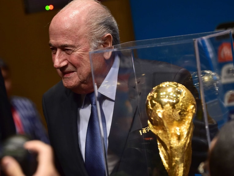 Joseph Blatter, poses next to FIFA World Cup trophy