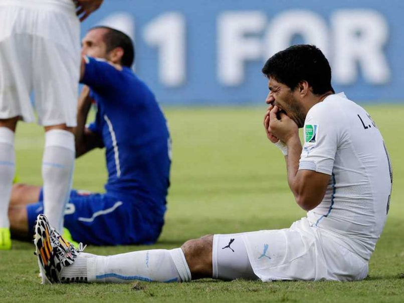 Uruguays Luis Suarez reacts after biting Italian defender Giorgio Chiellini during a 2014 FIFA World Cup match.