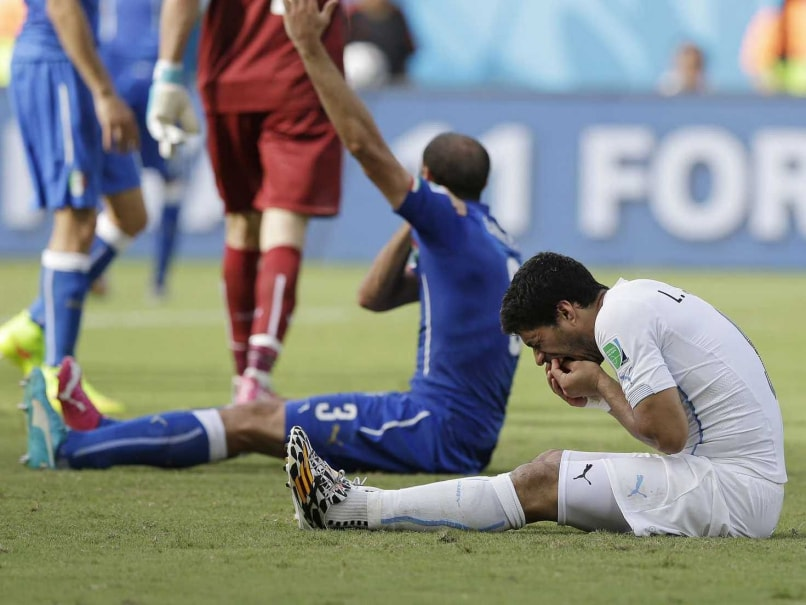 Uruguays Luis Suarez holds his teeth after running into Italys Giorgio Chiellinis shoulder during the group D World Cup soccer match between Italy and Uruguay at the Arena das Dunas in Natal, Brazil, Tuesday, June 24, 2014.
