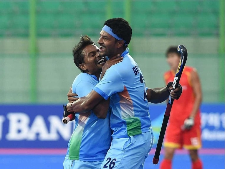 Indias Birendra Lakra (R) celebrates a goal against China with a teammate during their mens field hockey match at the Seonhak Hockey Stadium during the 17th Asian Games in Incheon on September 27, 2014.