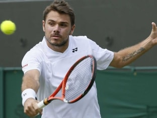 Stanislas Wawrinka plays a backhand stroke during Wimbledon 2014